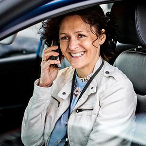 Heidi Isachsen sitter i bilen og snakker i mobilen